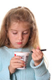 Little girl looking at her yogurt vertical Royalty Free Stock Image