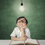 Little girl looking at light bulb in classroom Royalty Free Stock Photos