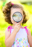 Little girl is looking through magnifier Stock Images