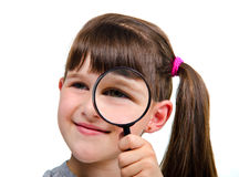 Little girl looking through a magnifying glass Stock Photo