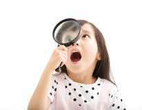 Little girl looking through  magnifying glass Royalty Free Stock Photos