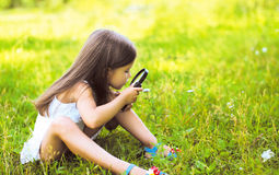Little girl looking through a magnifying glass. On flower Royalty Free Stock Photo