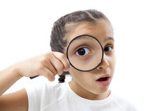Little girl looking through a magnifying glass Royalty Free Stock Photo
