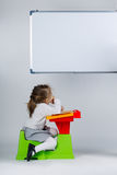 Little girl looking at marker board Royalty Free Stock Photos