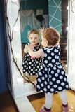 Little girl looking in the mirror. Happy little girl in the room looking in the mirror while playing royalty free stock image