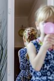 Little girl looking in the mirror at home wearing a skirt and a necklace.  royalty free stock images