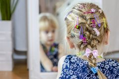 Little girl looking in the mirror at home wearing a skirt and a necklace.  royalty free stock photo