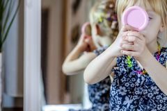 Little girl looking in the mirror at home wearing a skirt and a necklace.  stock image