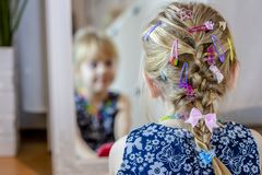 Little girl looking in the mirror at home wearing a skirt and a necklace.  royalty free stock photos