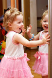 Little girl looking in the mirror. And laughing royalty free stock images
