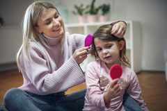 Little girl looking on mirror. Mother combing her little daughter. Mother and daughter at home. Close up stock photo