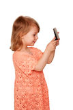Little girl looking in the mirror. Side view. Stock Photos