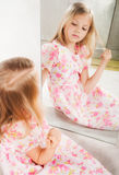 Little girl looking at mirror, studio portrait. Beautiful blond child Stock Images