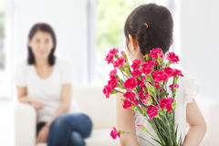 Little girl looking at mother and hiding a bouquet of carnations Stock Images