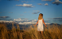 Little girl looking into a mountain landscape Royalty Free Stock Image