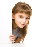Little girl is looking out from the blank banner Royalty Free Stock Images