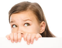 Little girl is looking from out blank board. Isolated over white Stock Image