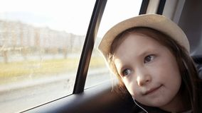 Little girl looking out from car window at sunny day. stock photography