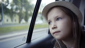 Little girl looking out from car window at sunny day. stock photo