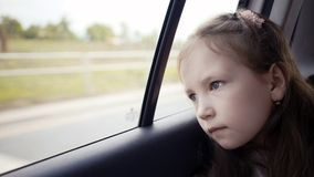 Little girl looking out from car window at sunny day. stock photos