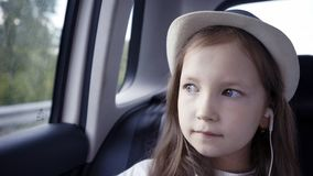 Little girl looking out from car window at sunny day. stock images