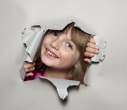 Little girl looking out of a hole Royalty Free Stock Photo