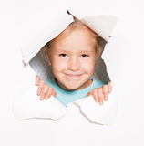 Little girl looking out of a hole in paper. Child looking out of a hole in paper. Banner. Happy girl Royalty Free Stock Images