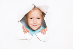 Little girl looking out of a hole in paper Royalty Free Stock Images