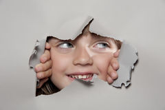 Little girl looking out of a paper hole Stock Images