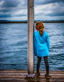 Little girl looking out to lake Stock Photo