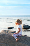 Little girl looking out to sea Stock Photo