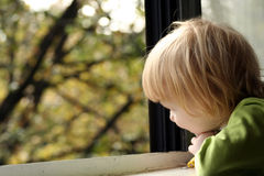 Little girl looking out window Royalty Free Stock Photography