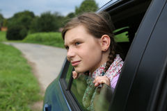 Little girl looking out from the window of a car Stock Photography