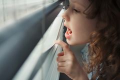 Little girl looking out window and crying. Stock Image