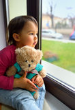 Little girl looking out the window Stock Photo