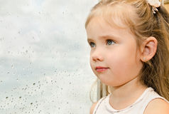 Little girl looking out the window on a rainy day Royalty Free Stock Images