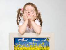 Little girl looking over computer monitor Royalty Free Stock Image