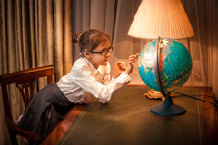 Little girl looking patiently at globe Royalty Free Stock Photos