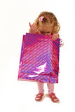 Little girl looking into a pink shopping bag Royalty Free Stock Images