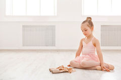 Little girl looking at pointe shoes, copy space Royalty Free Stock Photo