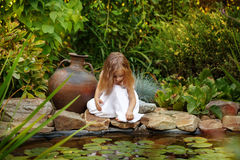 Little girl looking into a pond with lilies Stock Images