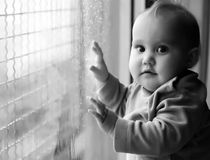 Little girl looking at raindrops Stock Photo