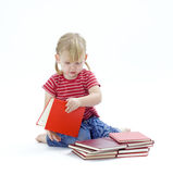 Little girl looking at red book Stock Photo