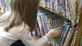 Little girl looking through rows of children's books stock footage