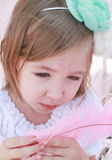 Little girl looking sad with a pink feather in hands Royalty Free Stock Image