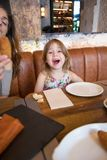 Little girl looking and screaming in restaurant Stock Images