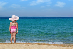 Little girl looking at sea. Little girl with straw hat looking at sea Stock Photos