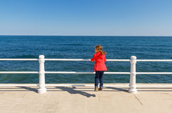 Little girl looking the sea. Little girl with red jacket jumping while looking at sea Royalty Free Stock Image