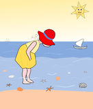 Little girl looking for sea shells Stock Images