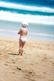 Little girl looking at sea standing on beach. Girl looking at sea while standing on the beach Royalty Free Stock Photo